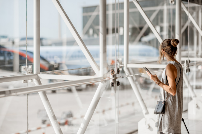 Woman at airport contemplating if I should travel for rehab